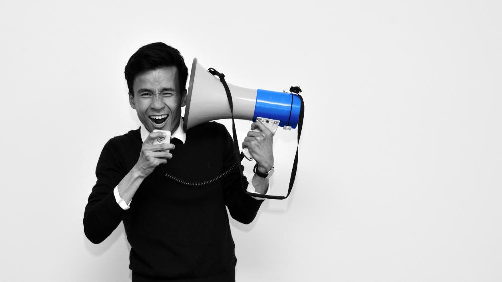 Christopher Trung Paulsen fra Slagelse Byråd i Slagelse Kommune med en megafon og omkring Ytringsfrihed